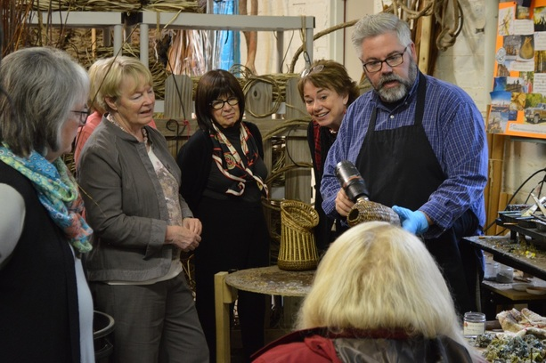 Matt Tommey of Asheville, North Carolina's River Arts District shows a group how he covers his handcrafted art basket sculptures with encaustic wax.