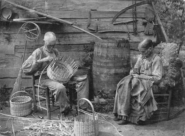Early Appalachian weavers sitting weaving together. Man and woman weaving baskets.