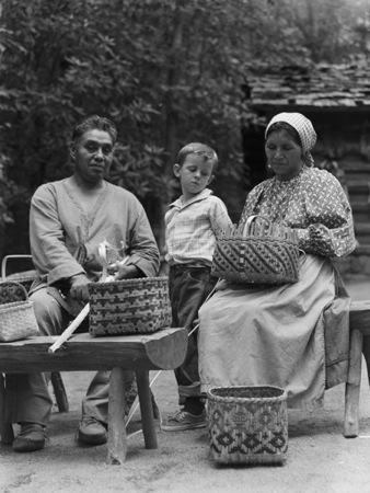 Cherokee Native American weaver family posing for a photo. Native American baskets being handwoven by man and woman.